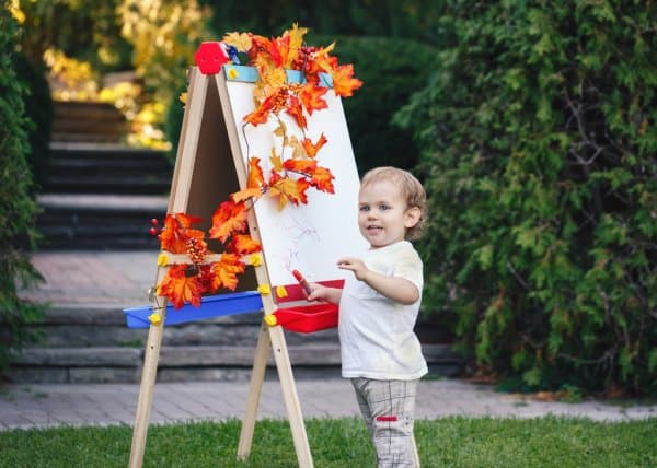 kid drawing with standing easel