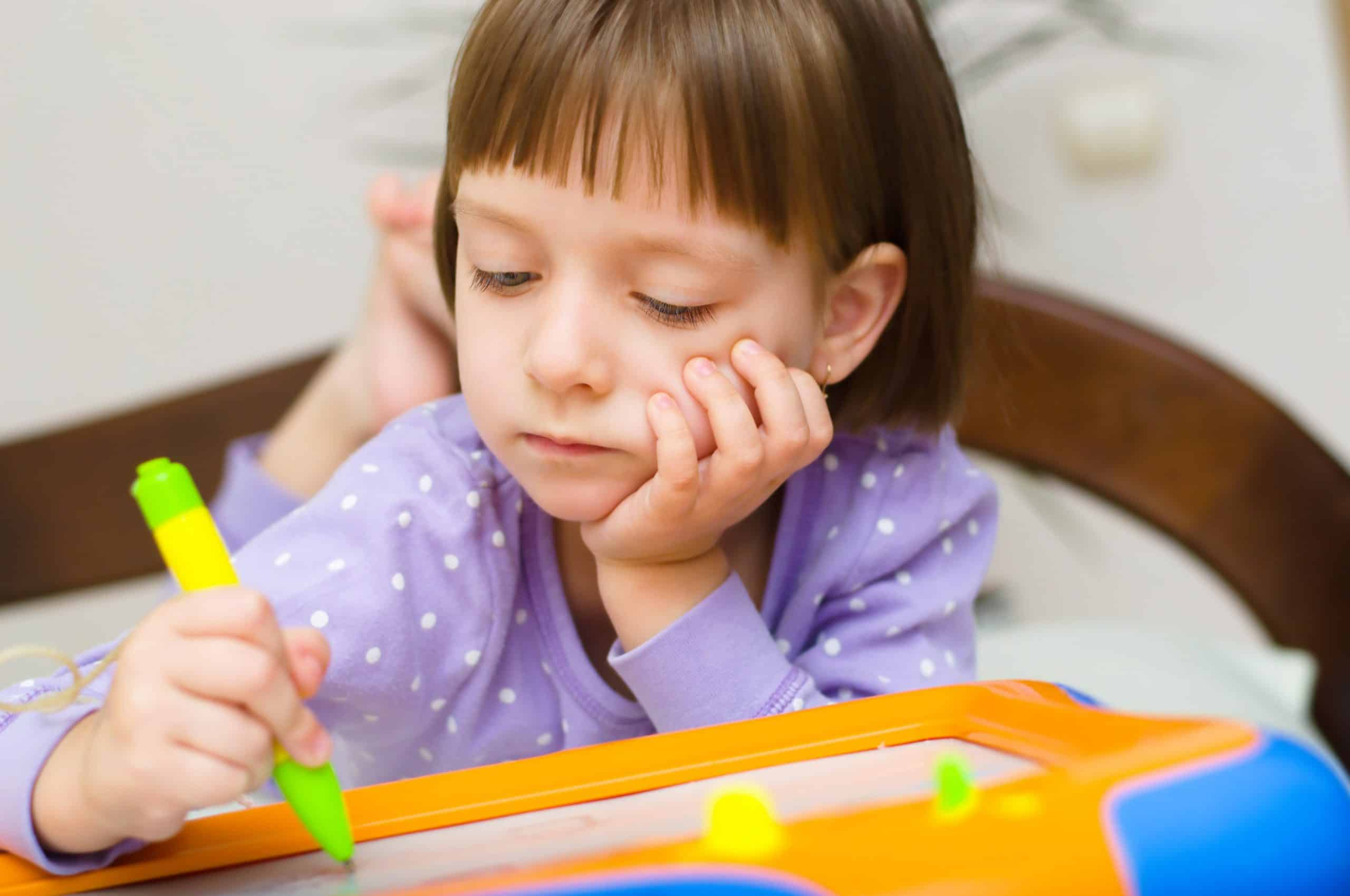 Little girl writing at magnetic drawing board