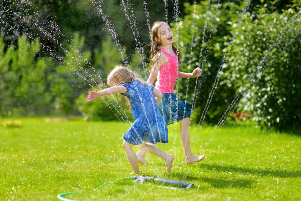 Adorable little girls playing with a sprinkler in a backyard on sunny summer day