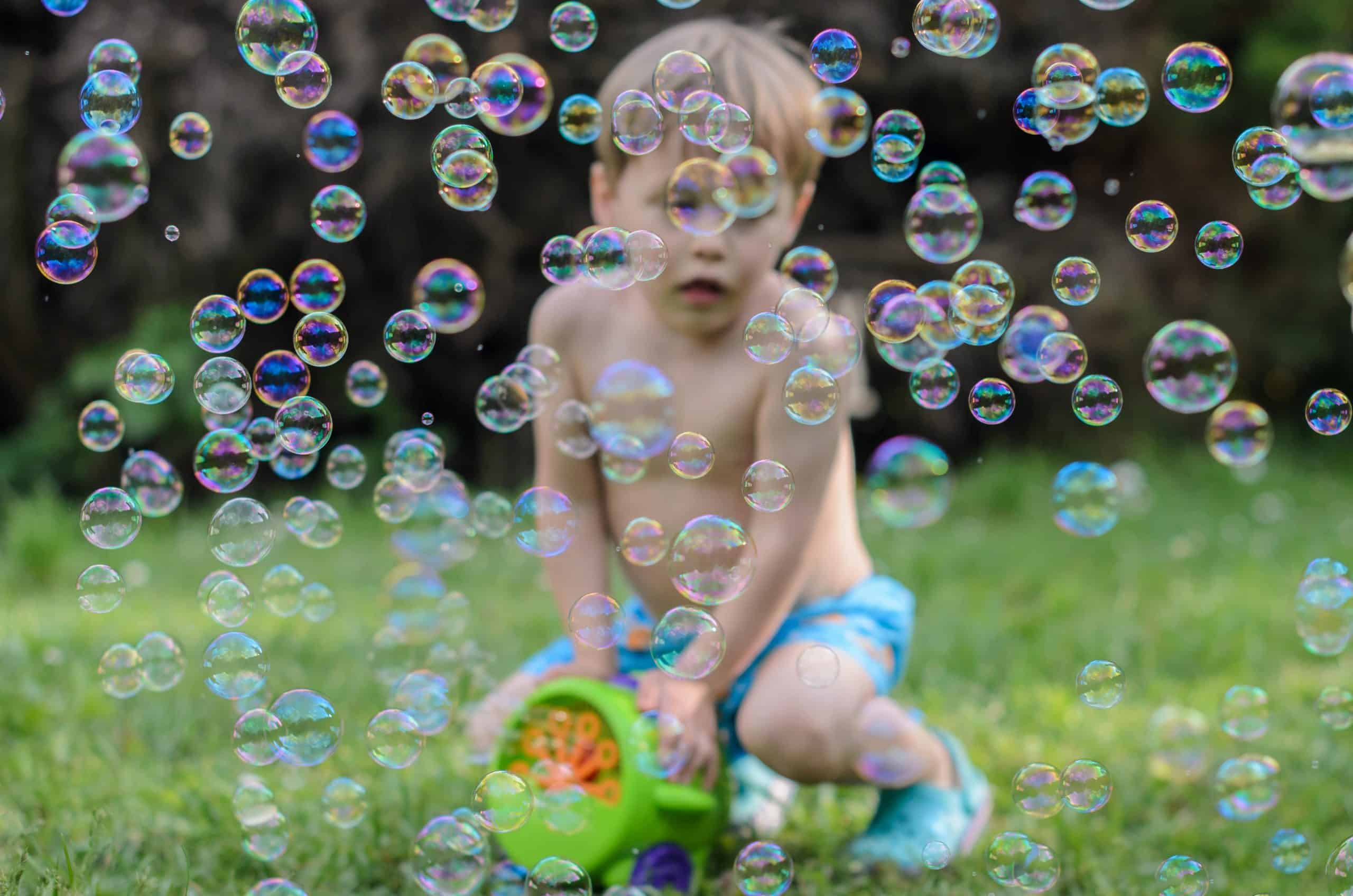 Blure boy plays with soap bubbles maker machine in the courtyard