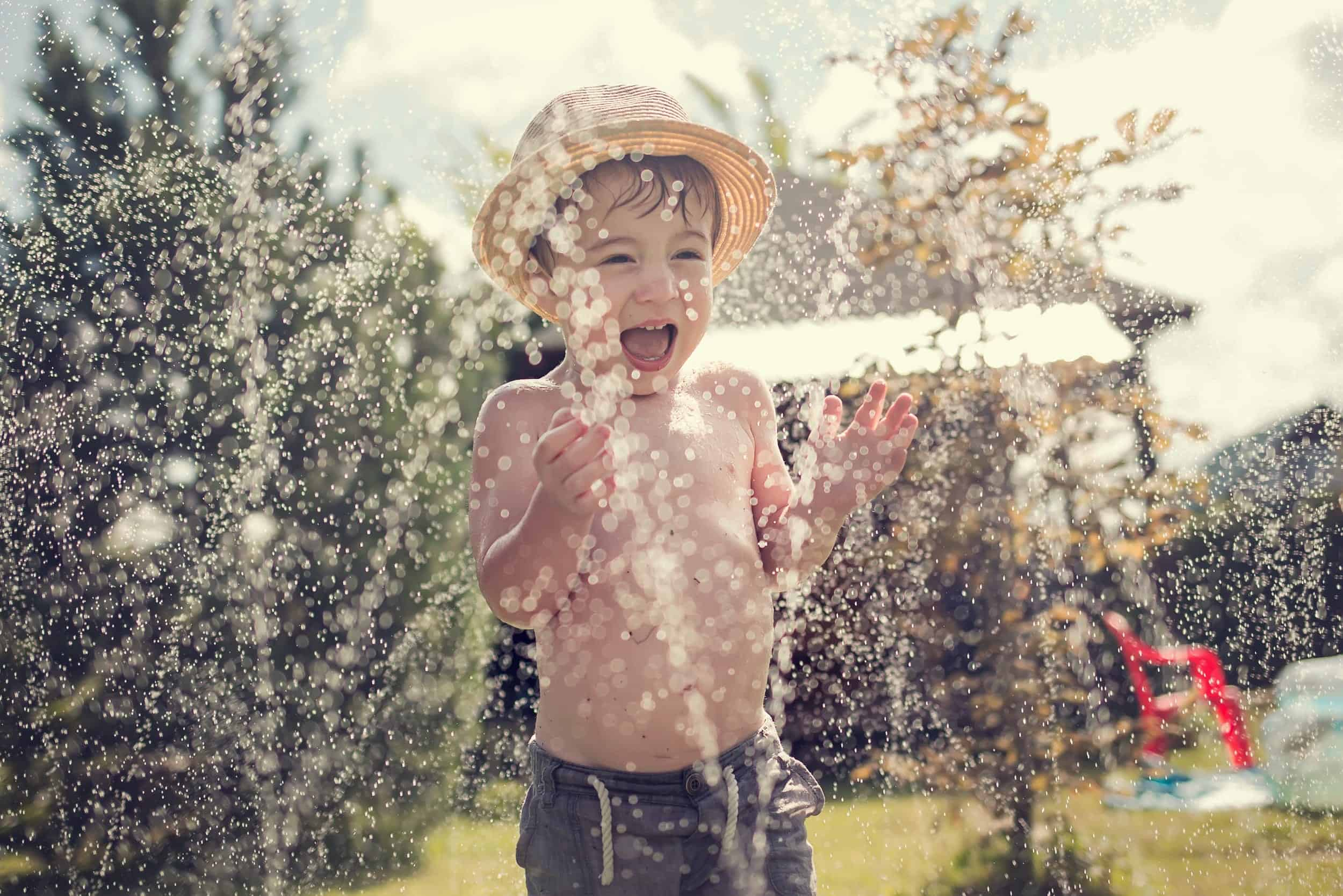 Cute little boy in straw hat is laughing and having fun running under water spraying hose.
