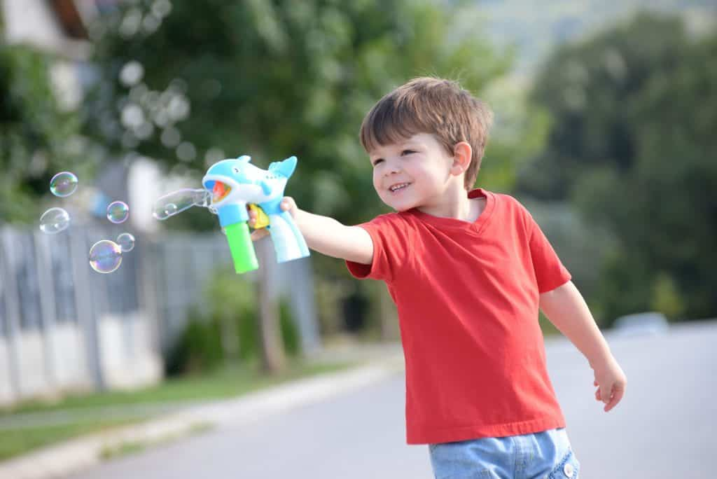 Little boy playing with soap bubbles machine on the street.
