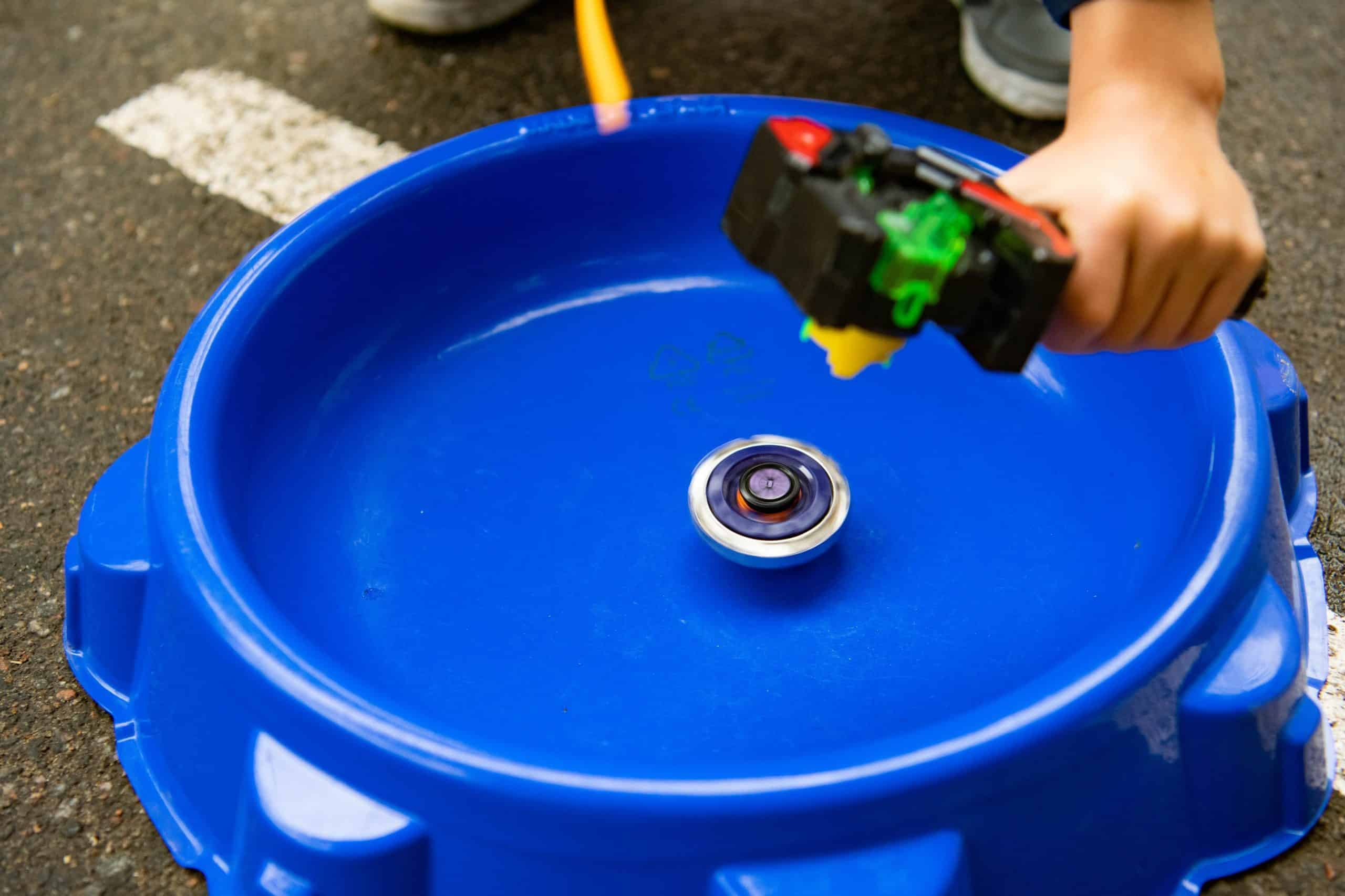The beyblade starter with beyblade (spinning tops) in the blue arena